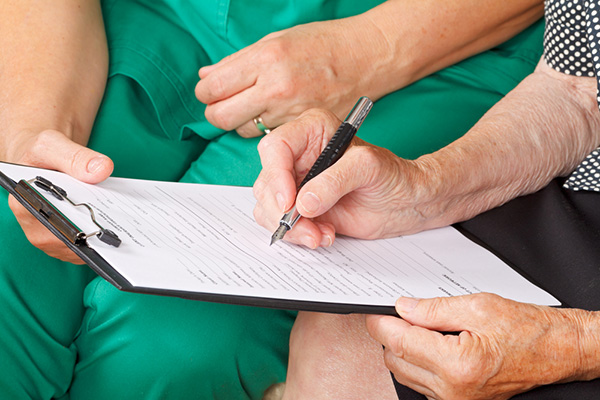 Man's hands filling out paperwork on a clipboard