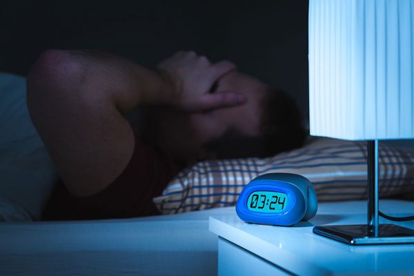 overweight man struggling to sleep