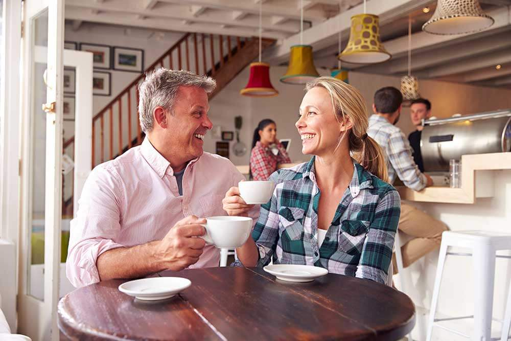 A man and woman smiling at each other on a coffee date