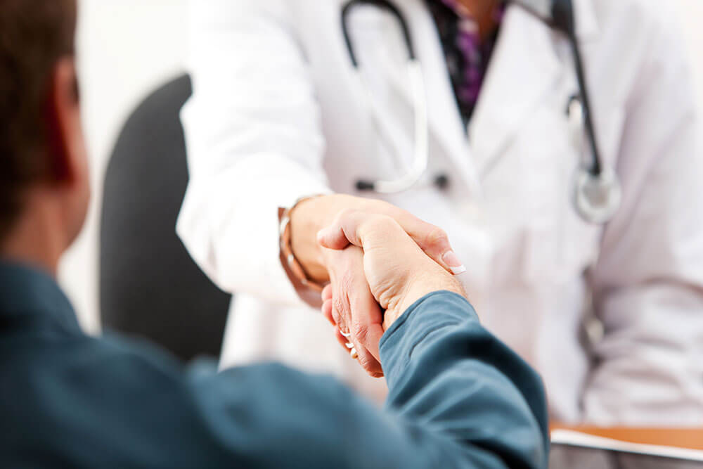 A close up of a doctor shaking hands with his patient